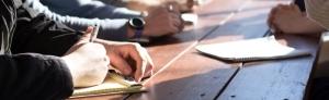 business meeting taking handwritten notes